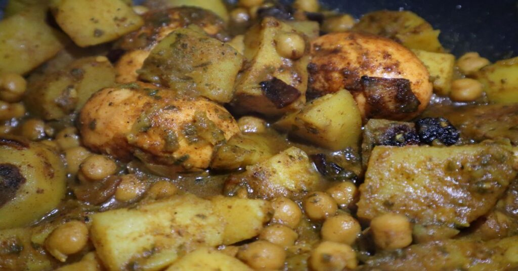 close up of egg curry recipe with hard boiled eggs, potatoes, and garbanzo beans in a pan