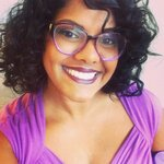 Salei The Natural Foodie food blogger smiling in purple lipstick and purple framed eyeglasses