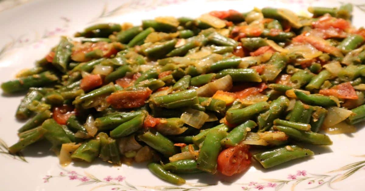 Sautee green beans with onions, garlic, and tomatoes