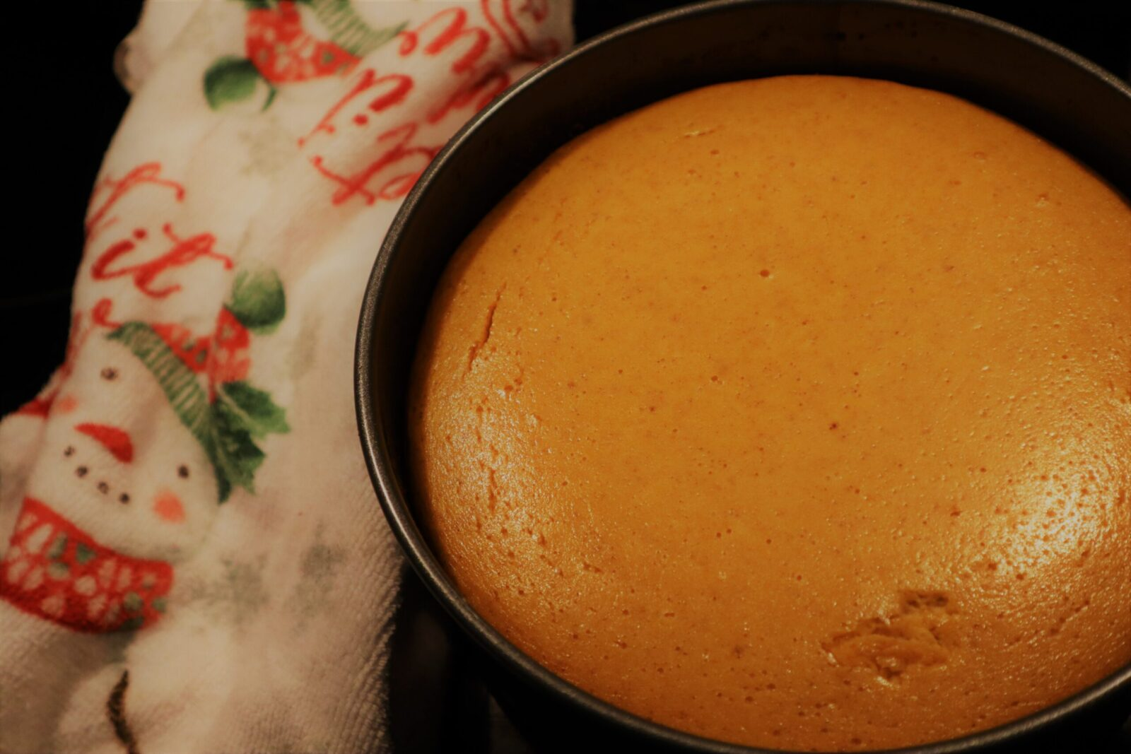 Pumpkin cheesecake in a springform pan next to a Christmas towel