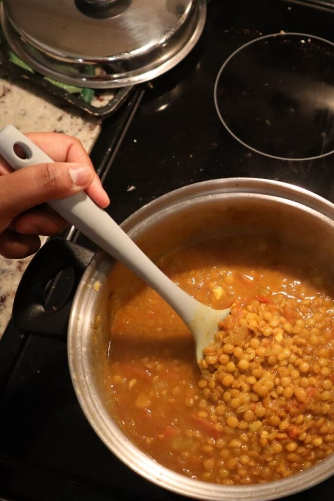 Lentils on black stovetop with cover off. Salei's hand stirring lentils with gray spoon.
