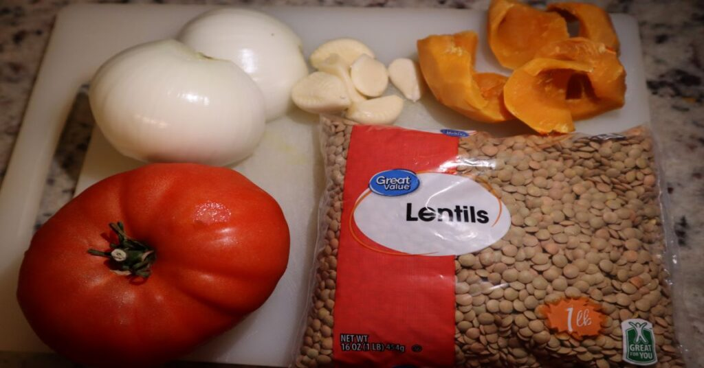 Ingredients for lentil recipe or lentil soup recipe: tomato, onion, garlic, dried lentils, and pumpkin