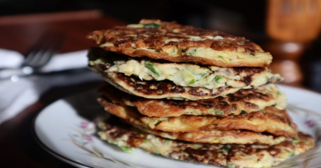 Savory Zucchini fritters/pancakes stacked on a white plate