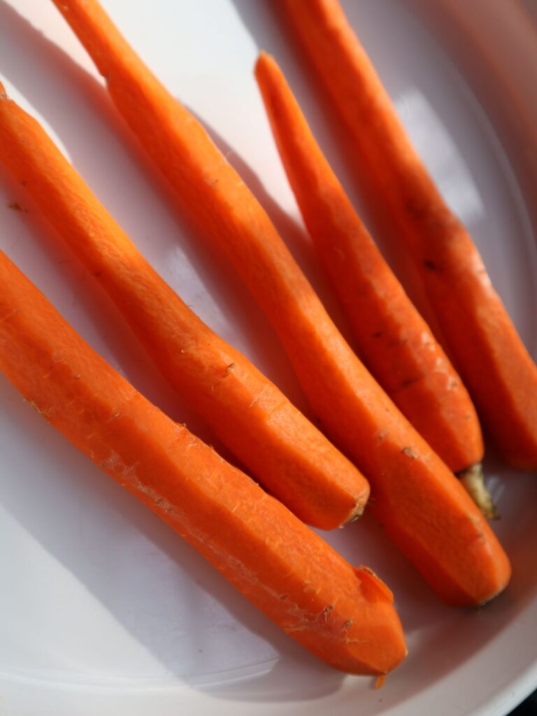 Whole carrots cleaned in a white baking dish