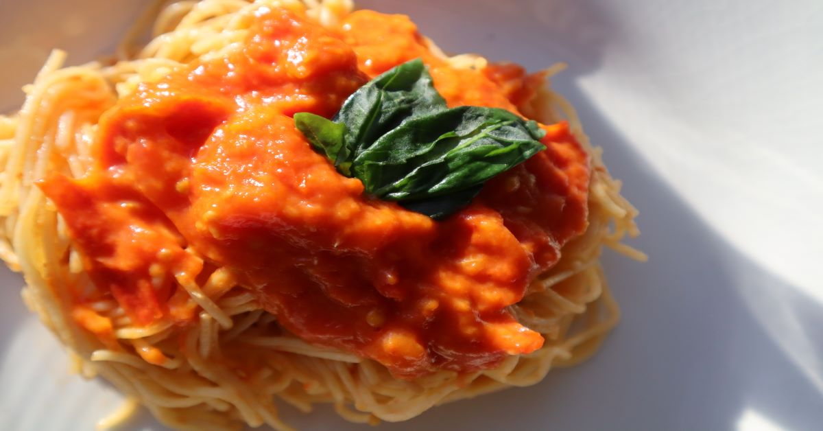 Angel Hair Pasta With Homemade Tomato Sauce topped with fresh basil