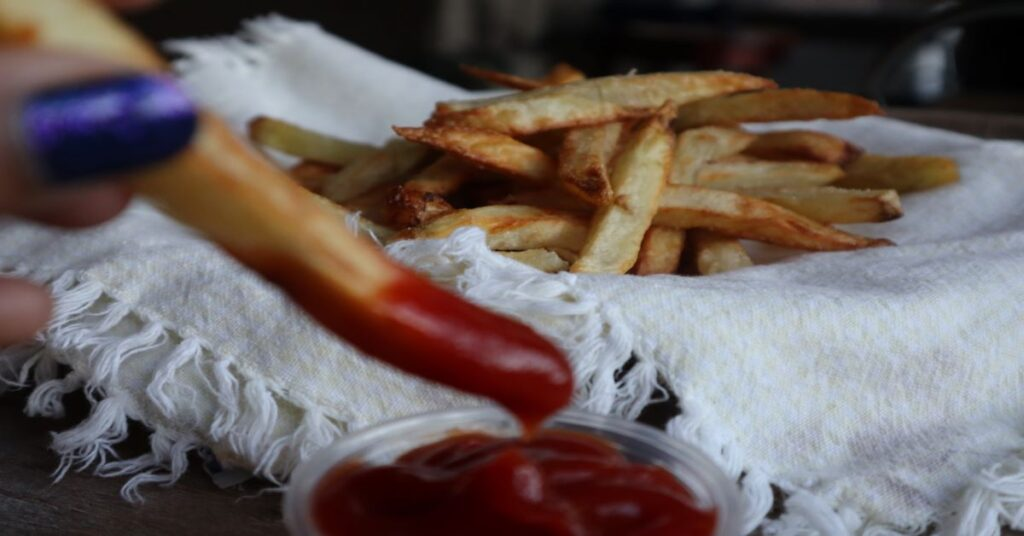 Crispy Homemade Air Fryer French Fries with one dipped in ketchup