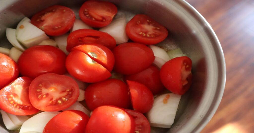 Pot filled with halved Campari tomatoes and onions