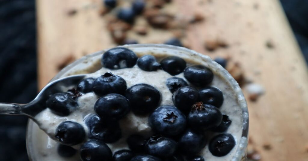 close up of cup with  a lot of bluerries on the spoon. Brown cutting board background with granola and blueberries spread around
