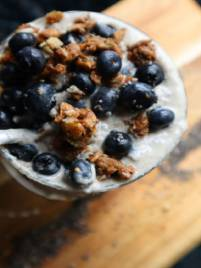 Cup of Chia Seed pudding with spoon in it topped with blueberries and granola on a light brown board background that has chia seeds spread on it
