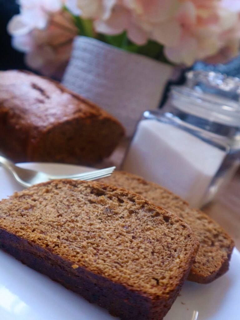 Two slices of vegan banana bread on a small white plate. Behind it is a banana, two gold forks, sugar in a clear jar and some pink hydrangeas in a white vase with the rest of loaf