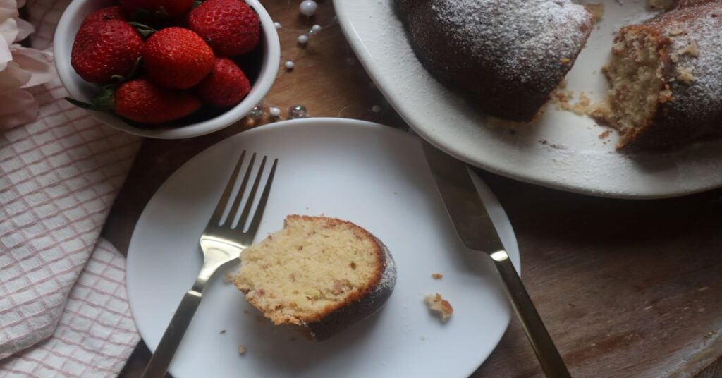 Strawberry champagne pound cake slices with rest of cake on white plate and strawberries in small cup in background