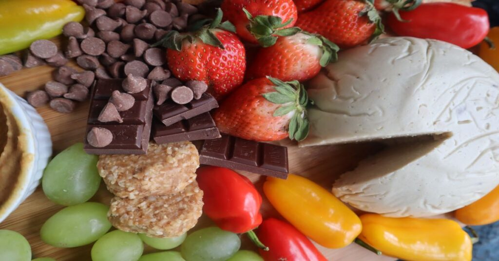 Vegan Cheese Recipe displayed on a fruit and veggie board (strawberries, green grapes, mini bell peppers in red and yellow, and chocolate)