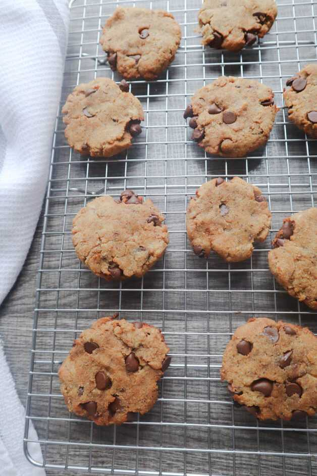 Vegan Banana Chocolate Chip Cookies on cooling rack with kitchen towel along left side