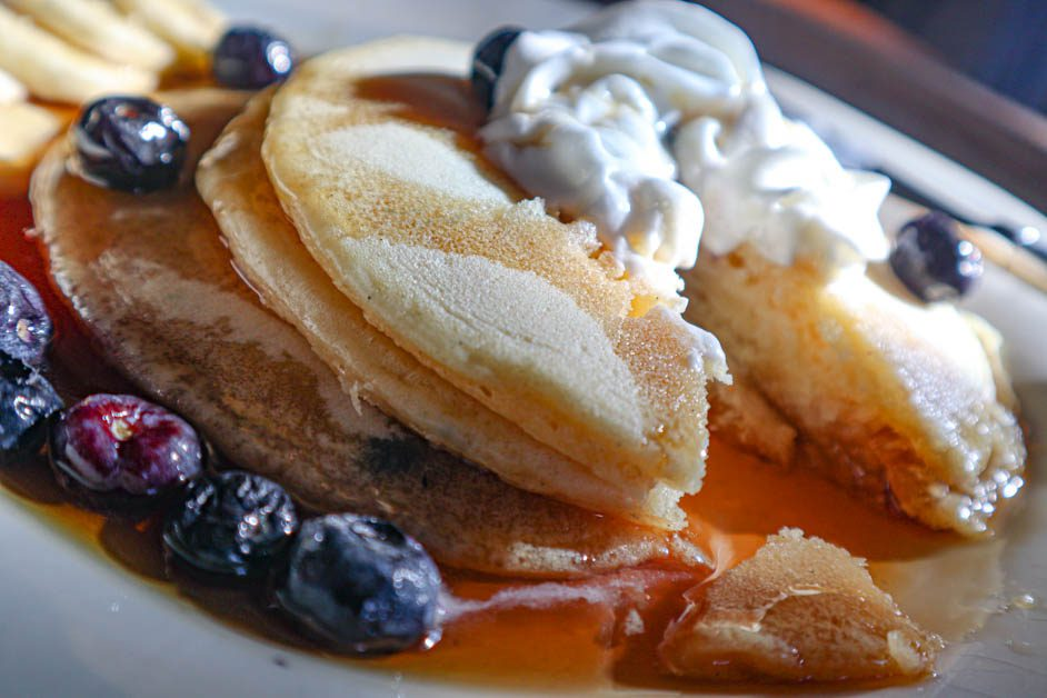 Short stack of pancakes topped with whipped cream and blueberries in a pool of maple syrrup