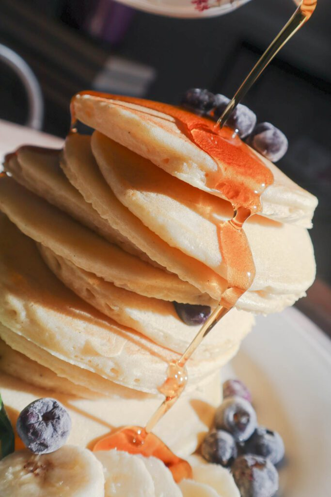 Stack of pancakes with maple syrup being poured onto it. Topped with fresh blueberries