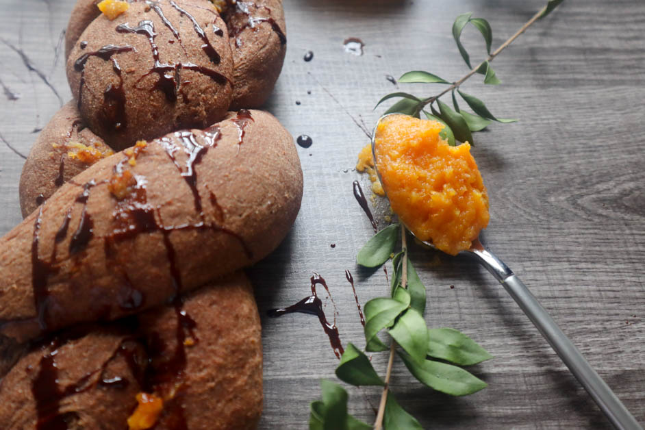 Chocolate Orange Braided Bread drizzled with chocolate syrup on a gray textured background with a silver spoon filled with orange marmalade on it.