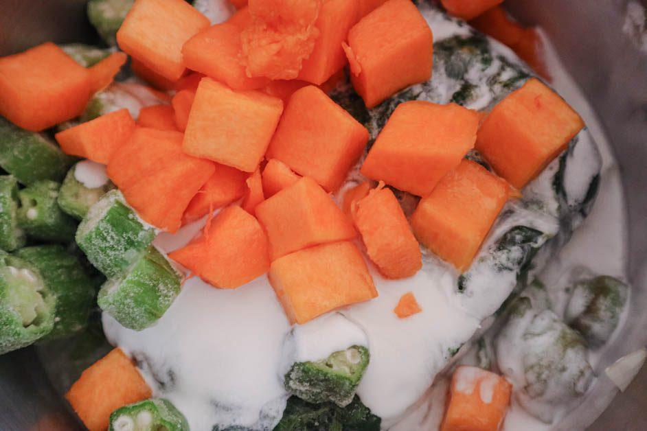 Coconut milk. pumpkin, okra in large pot