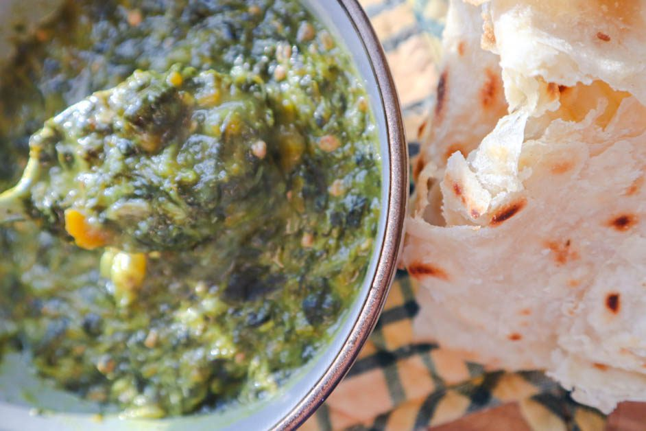 Callaloo in gray bowl next to some roti . Yellow and green checkered pan handle cover in background