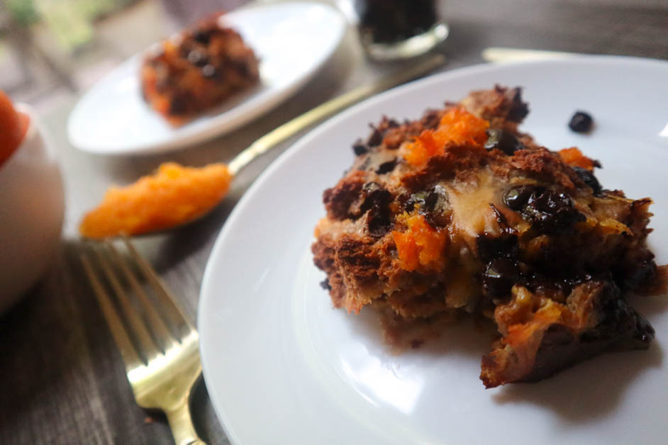 Chocolate orange bread pudding in two separate white plates with a spoon of orange marmalade between them